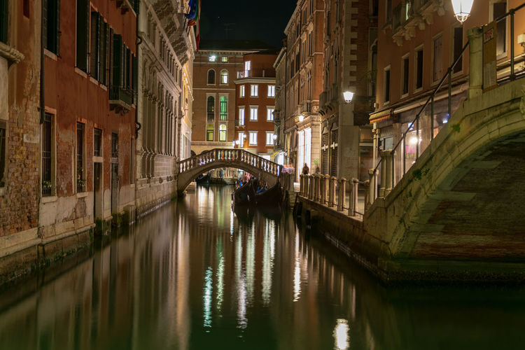 Bridge over canal amidst buildings in venice at night