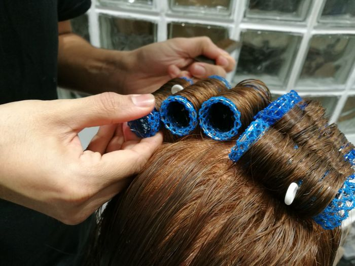 Cropped hands of hairdresser applying hair curlers on woman