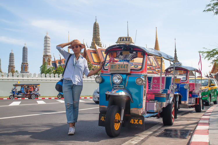 BANGKOK, THAILAND - April 16, 2019: Landmark, Wat Phra Kaew, Asian woman taking picture with Tuk Tuk, Signature of Thailand Summer Holiday Streetphotography Vacation Art Real People Architecture City Sky Built Structure Building Exterior Full Length Lifestyles Transportation Mode Of Transportation Incidental People Young Adult Leisure Activity Casual Clothing One Person Day Travel Adult Land Vehicle Outdoors Historic Parking Mode Of Transport Urban Scene Visiting