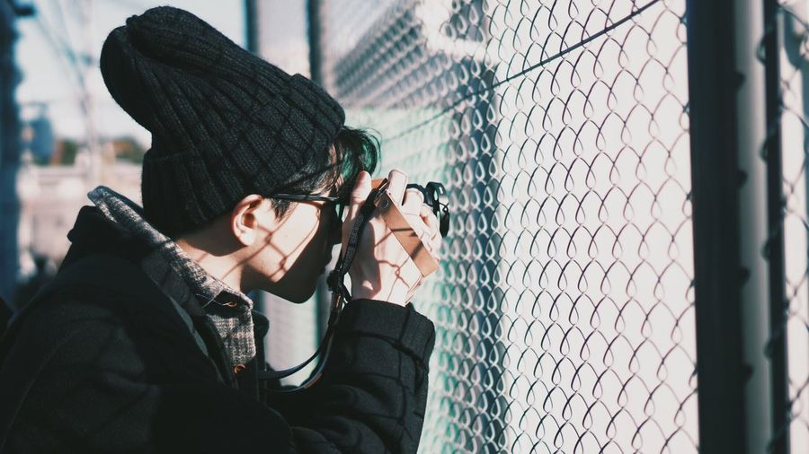 Side View Of Man Photographing With Camera By Chainlink Fence