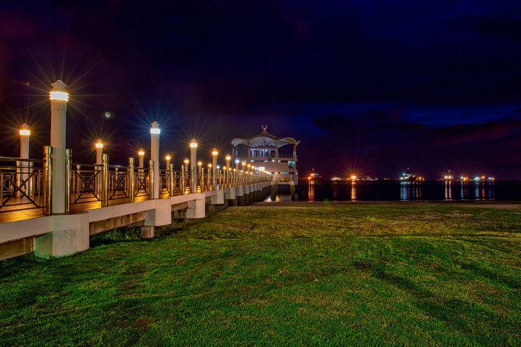 Illuminated street lights by bridge in city at night