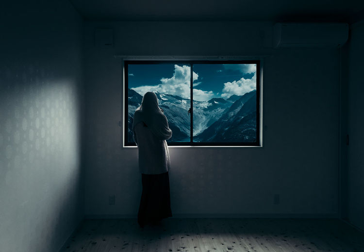 Rear View Of Woman In Room Looking At Mountains Through Window