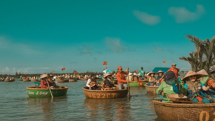 People on boats in sea against sky