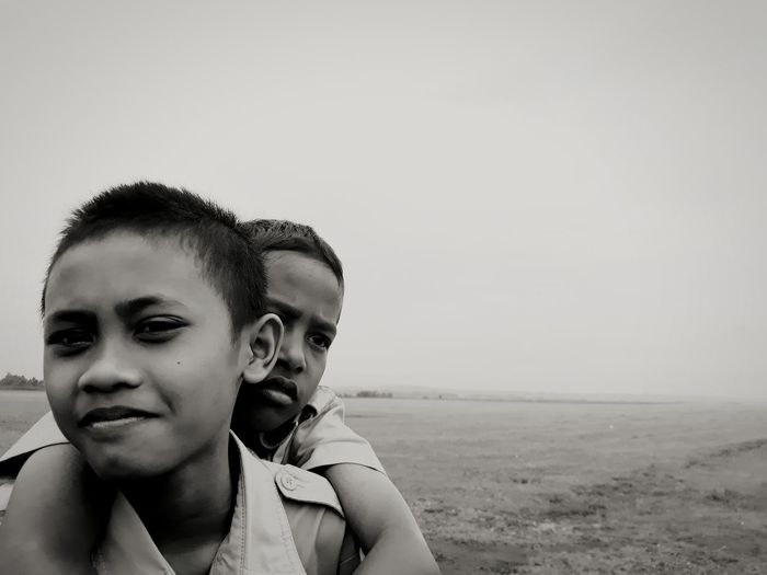 Portrait Of Boy Piggybacking Brother Against Sky