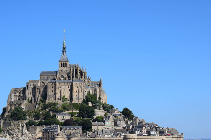 Le Mont Saint Michel, France Ancient Civilization Architecture Blue Building Building Exterior Built Structure City Clear Sky Copy Space Day History Low Angle View Nature No People Outdoors Place Of Worship Religion Sky Spire  The Past Tower Travel Travel Destinations