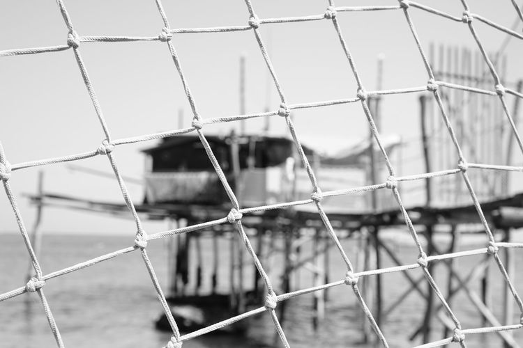Detail shot of fence against blurred stilt structure in water