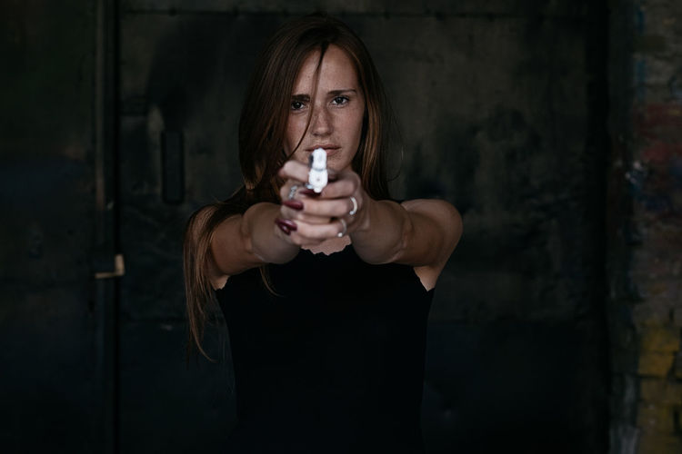 Portrait of a beautiful ginger female model with gun Alone Gun Horizontal Adult Beautiful Woman Casual Clothing Danger Dangerous Drink Focus On Foreground Freckles Front View Ginger Holding Indoors  Killer Looking At Camera One Person Portrait Real People Revange Sexygirl Standing Young Adult Young Women