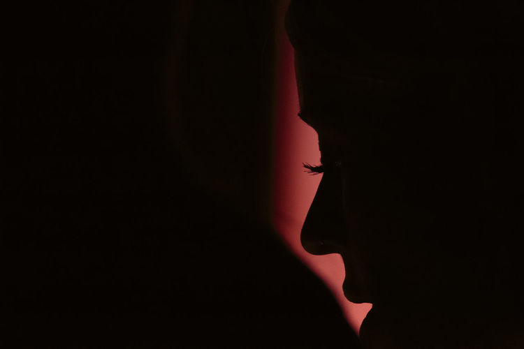 Close-up of silhouette hand against black background