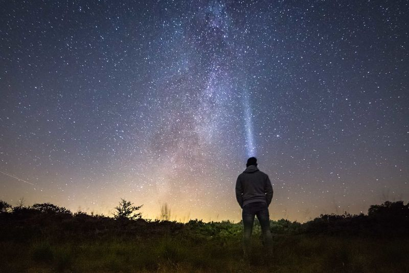 Rear view of man with illuminated headlamp against star field