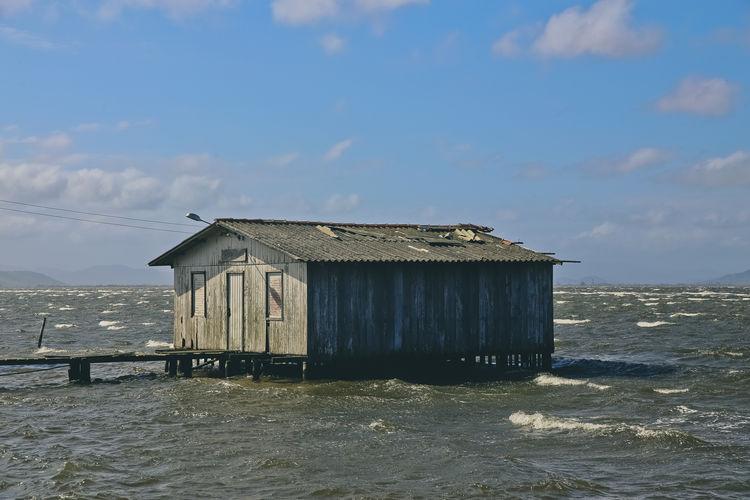 Wooden house on beach by sea against sky
