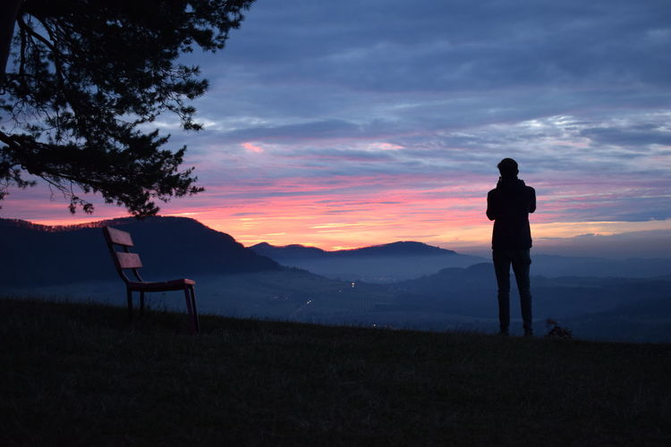 Silhouette man photographing on landscape against sky during sunset