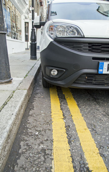 November 2017, London, England, a white van has parked on double yellow lines - a road sign that prohibits parking in England. Wheel Yellow Lines Building Exterior Car City Close-up Day Fine Illegal Land Vehicle Naughty Girl  No People Outdoors Parked Parking Parking Restrictions Penalty Prohibited Road Street Transportation Yellow