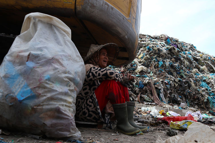 Midsection of man sitting by garbage against sky