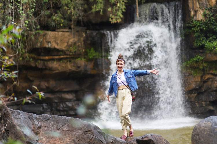 Portrait of smiling woman standing on rock against waterfall