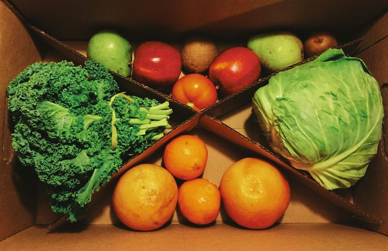 Directly above shot of vegetables and fruits in cardboard box