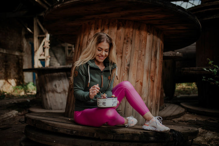 Young woman smiling while sitting on wood