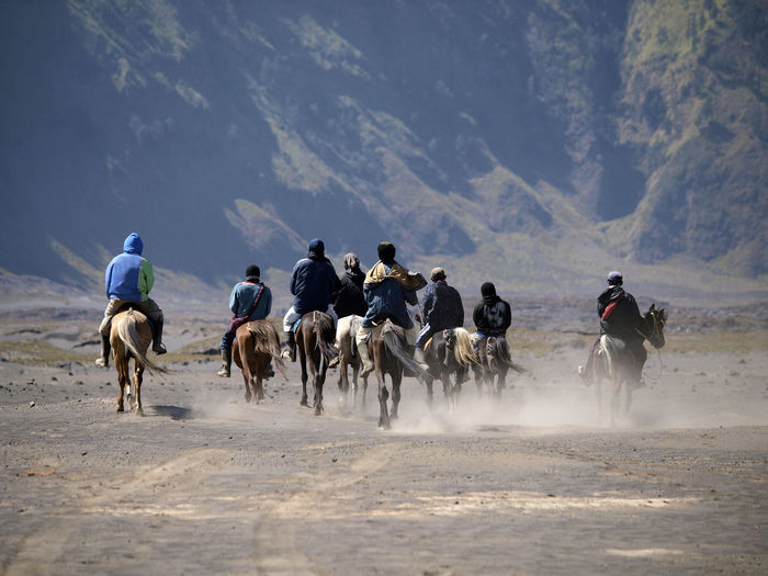 People Riding Horses On Landscape Against Mountains