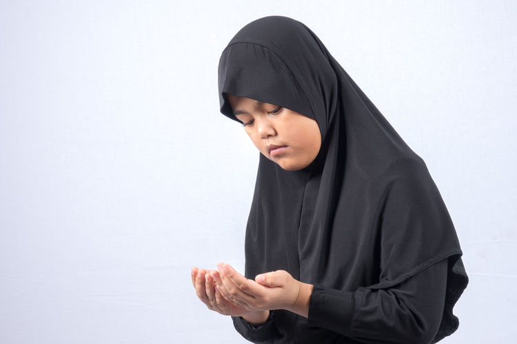 Girl In Hijab Praying Over White Background