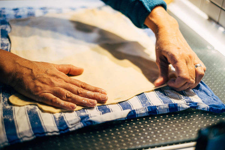 Close up of human hand prepairing dough on table