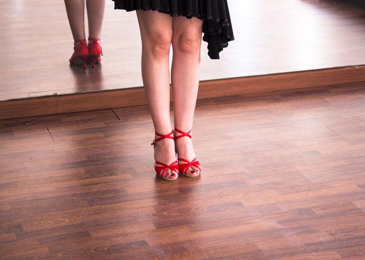Low section of woman in high heels standing on hardwood floor