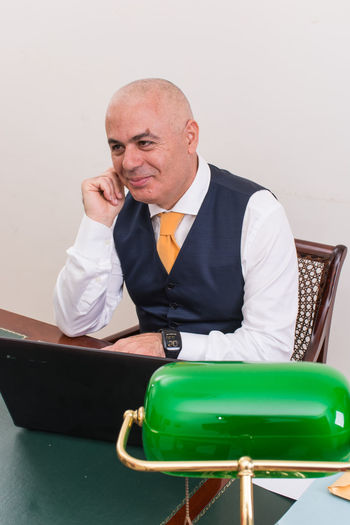 Smiling Businessman Sitting Laptop At Desk In Office