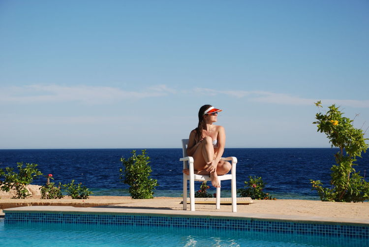 Young woman looking at swimming pool against sea