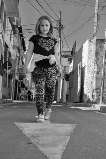 Portrait of girl standing on street in city