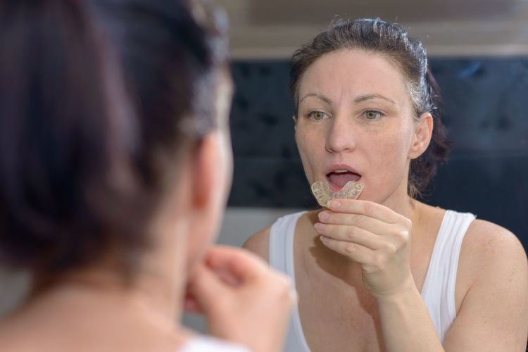 Reflection of woman holding dentures on mirror