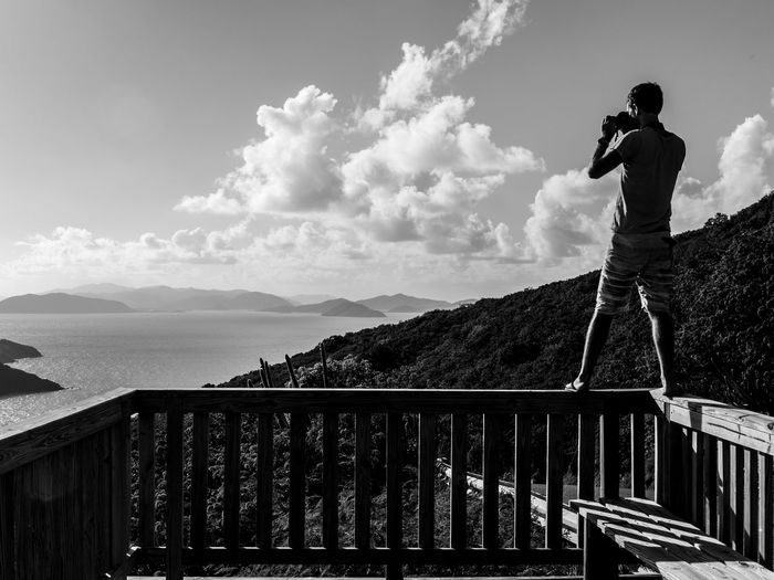 Man photographing through camera while standing on railing at observation point