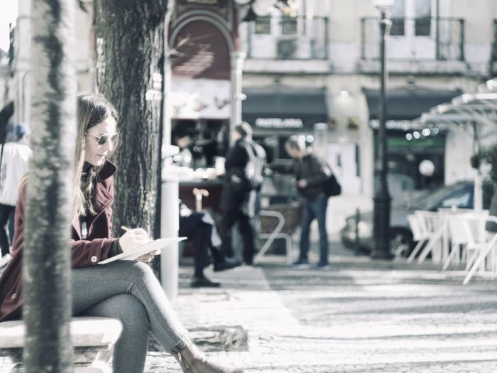 Sitting Young Adult Adult Incidental People Real People Day Architecture Women Casual Clothing Focus On Foreground People Reading City Full Length Lifestyles Three Quarter Length Cafe Young Women Leisure Activity Outdoors