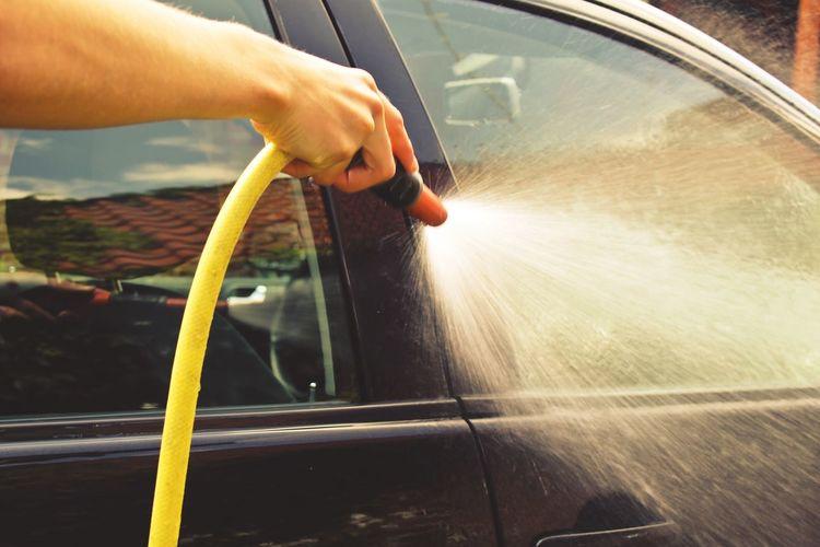 Cropped image of man washing car with gardening hose