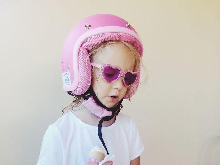 Cute girl in sunglasses wearing helmet against wall