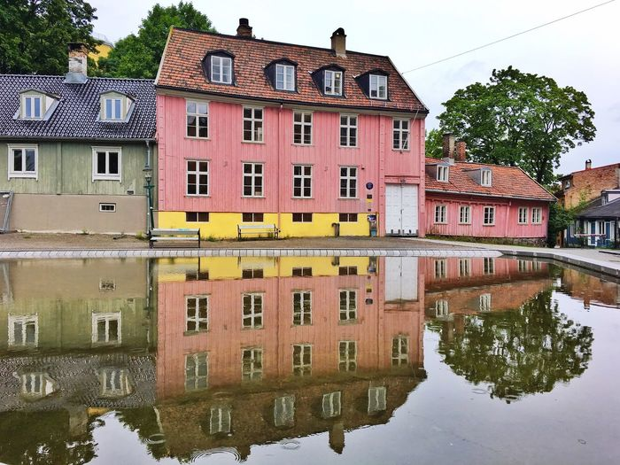 Reflection of house in puddle against sky