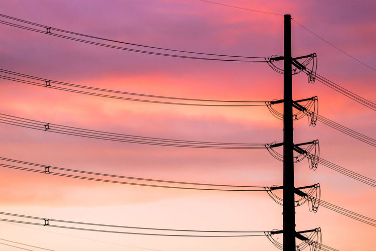 Low angle view of electricity pylon against pink sky during sunset