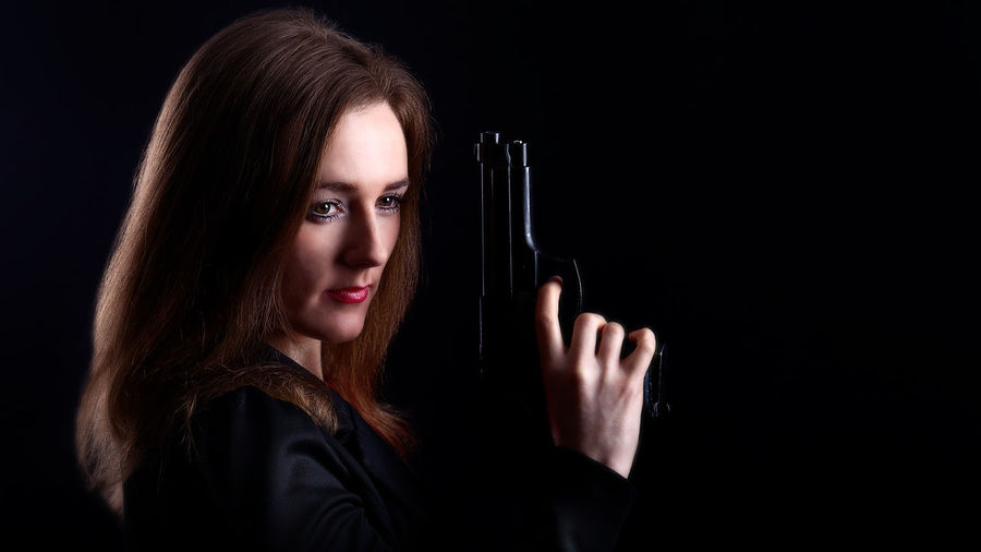 The Lady Waits. Irish Actress Sarah Mulligan styled as an F.B.I agent. Actor Actress Black Background Brunette Danger FBI Gun Guns Handgun Irish Low Key Police TRIGGER Undercover Waiting Determined Determined Face Determination Strong Woman