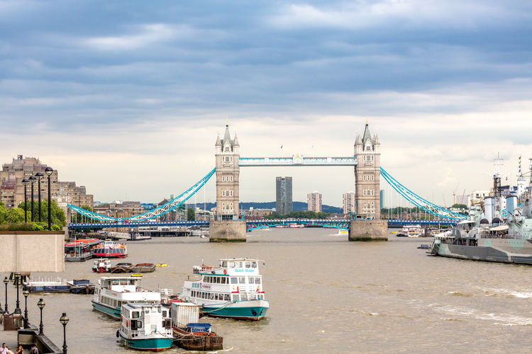 Tower bridge over thames river in city against sky