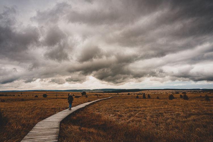 Woman walking on boardwalk amidst field against storm clouds