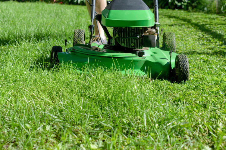 Low section of person with lawn mower on grassy field during sunny day
