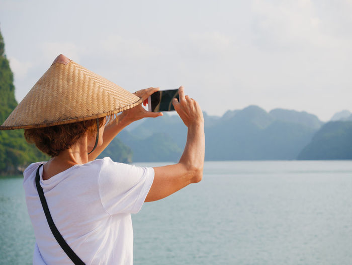 Rear view of person photographing sea against sky