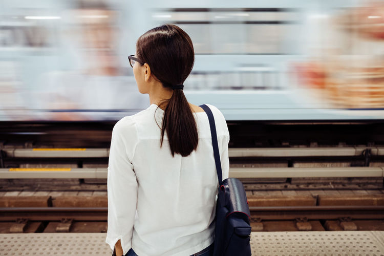 Woman standing by train at railroad station platform