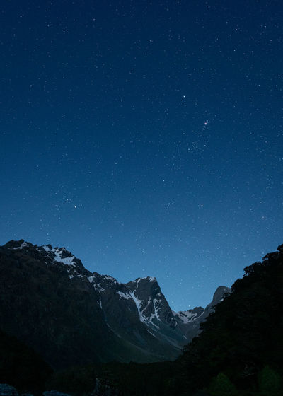 Scenic view of mountains against blue starry sky at night