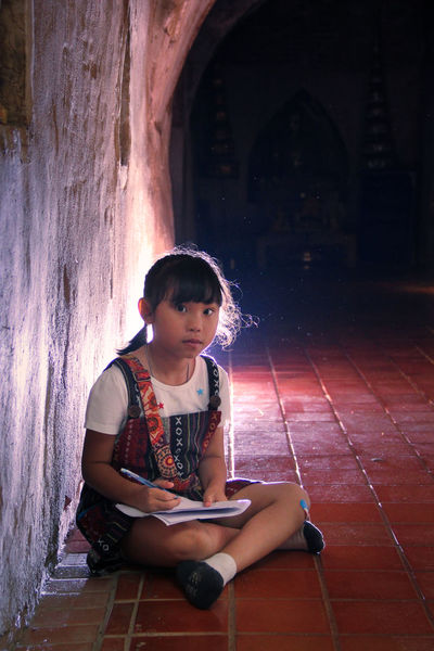 The girl explores the ancient tunnels and she takes notes into the notebook One Person Real People Girl Explorer Child Innocence Ancient Architecture Tunnel Notebook Take Note