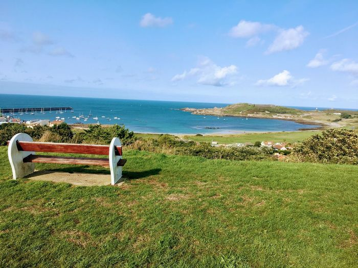 View of bench on beach against sky in alderney