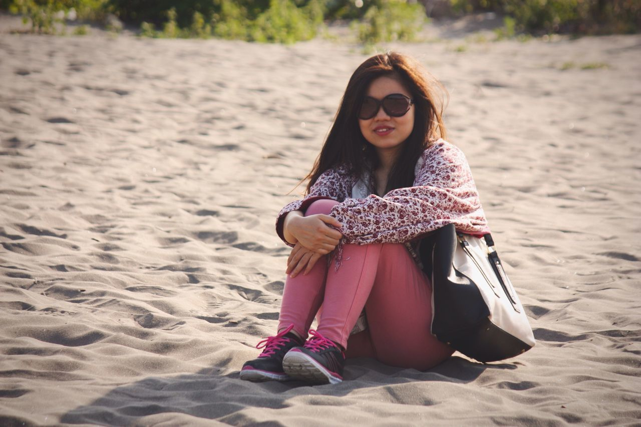 Beautiful Woman Sitting With Purse On Sand At Beach