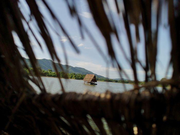 Stilt house in lake against sky
