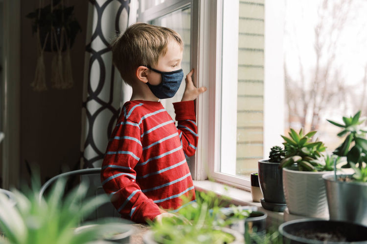 Boy looking at potted plant