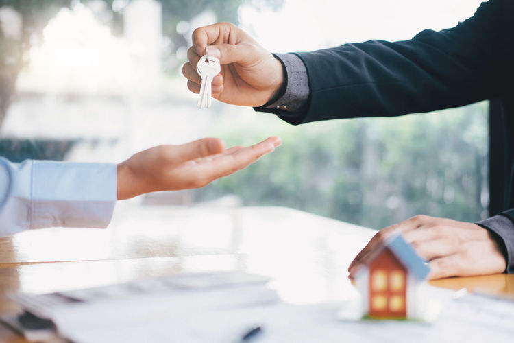 Cropped Hand Of Businessman Giving House Keys To Customer In Office