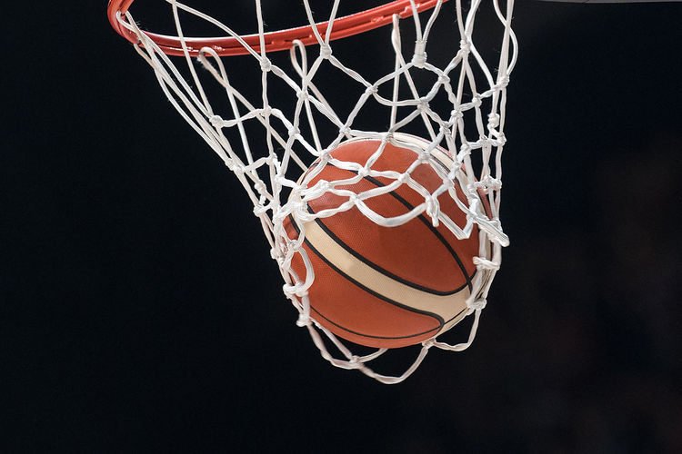 Low angle view of basketball hoop against black background