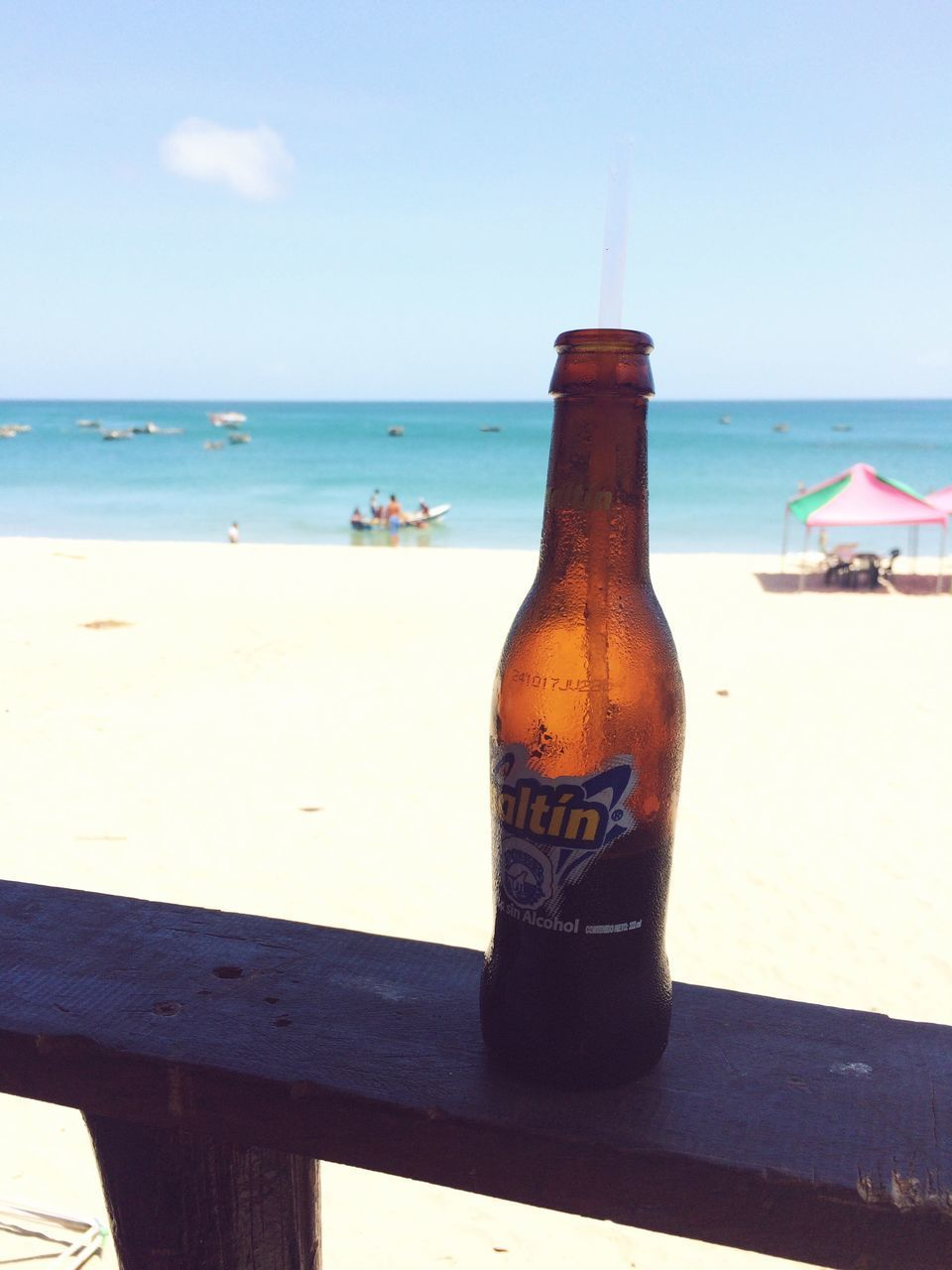 sea, beach, horizon over water, sand, water, bottle, table, sky, day, outdoors, nature, drink, summer, no people, vacations, sunlight, scenics, beauty in nature, close-up, alcohol
