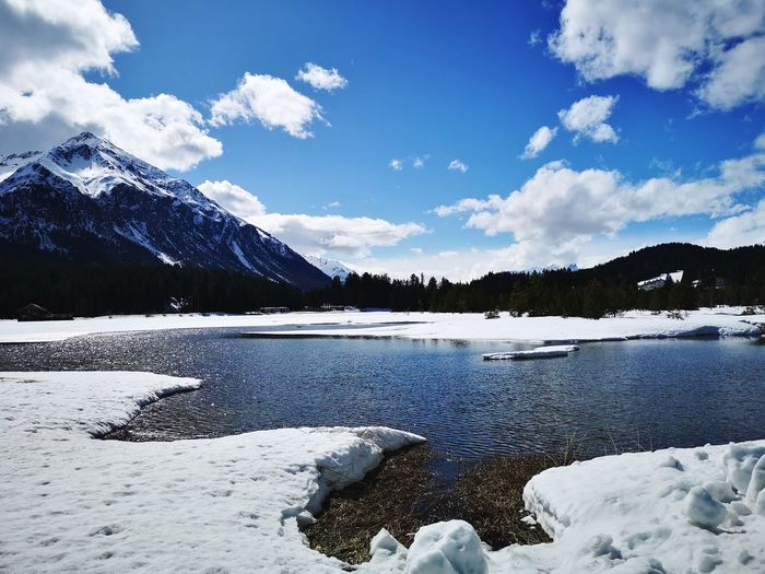 Scenic view of lake and snowcapped mountains against cloudy sky